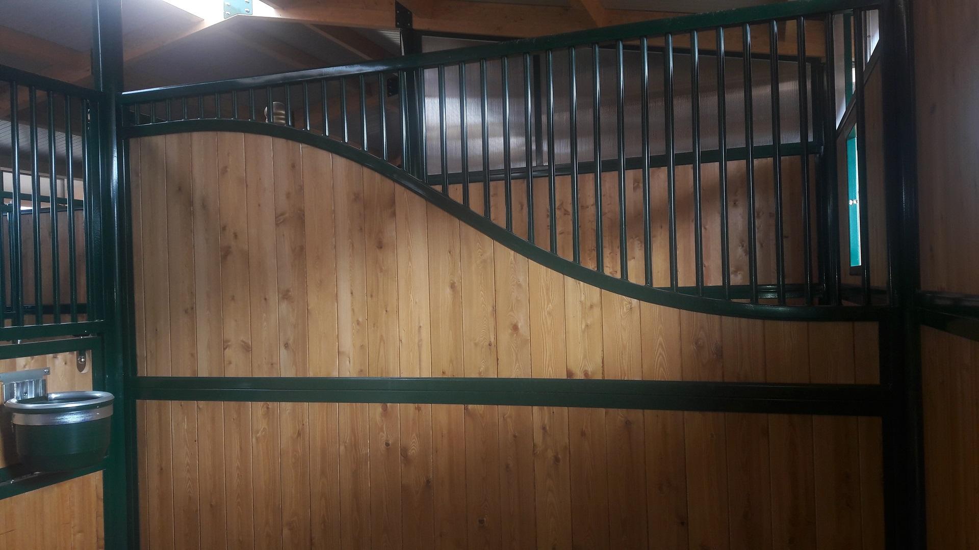 Divisorio con intelaiatura in ferro zincato e verniciato (sistema Triplex) tamponato a legno larice spessore 43 mm nella parte bassa, parte alta parzialmente tamponata a legno larice spessore 33 mm e parzialmente grigliata a barre